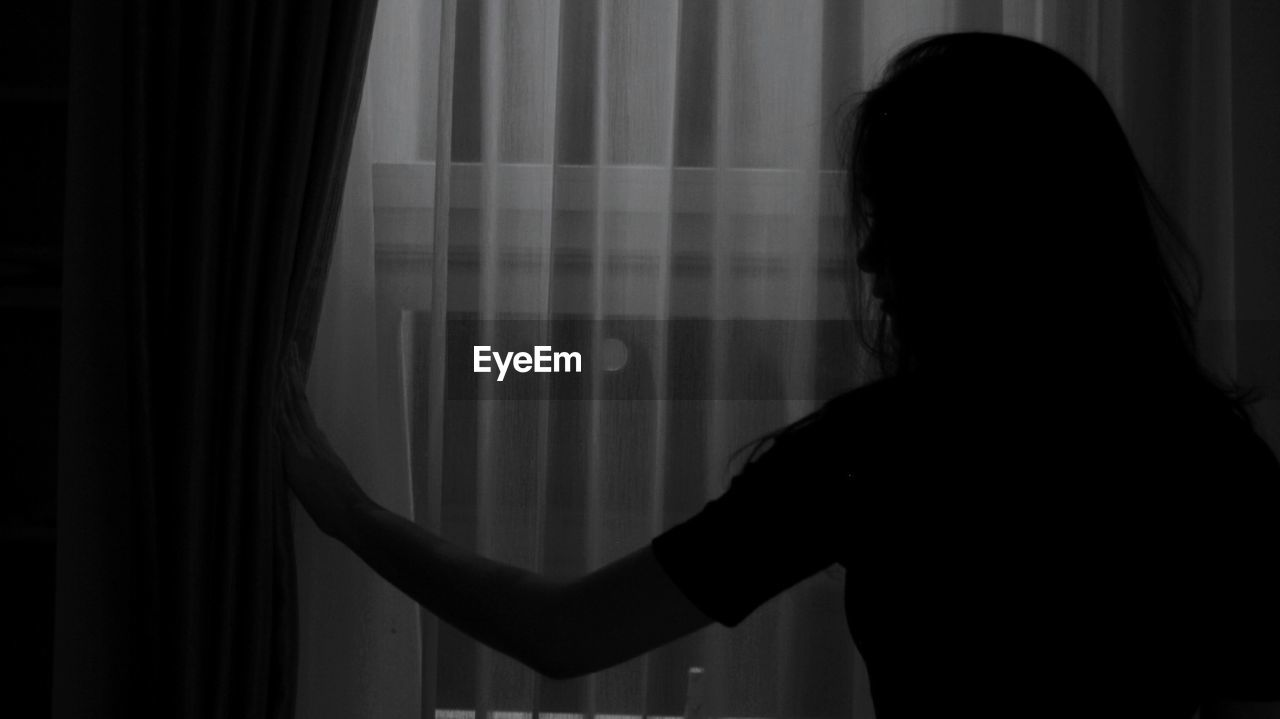 Rear View Of Silhouette Woman Standing By Window At Home