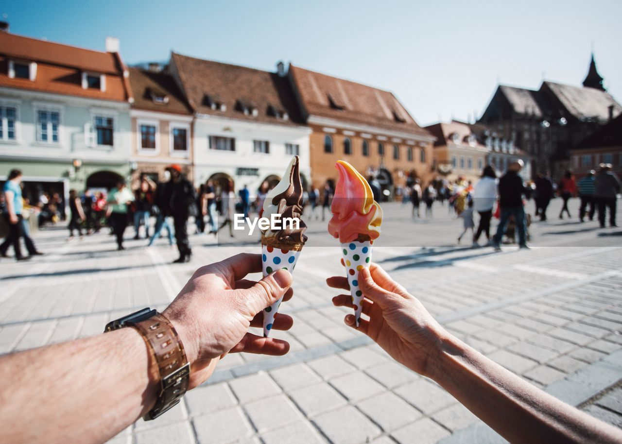 Cropped Hand Of Couple Holding Ice Cream Cones