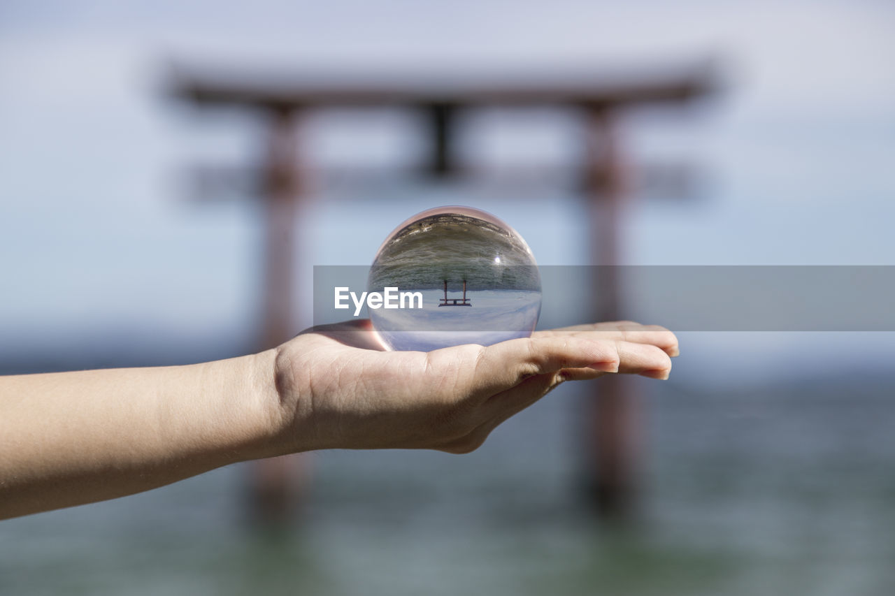 human hand, hand, focus on foreground, one person, human body part, sphere, water, holding, crystal ball, unrecognizable person, close-up, day, nature, glass - material, finger, body part, human finger, real people, outdoors, human limb