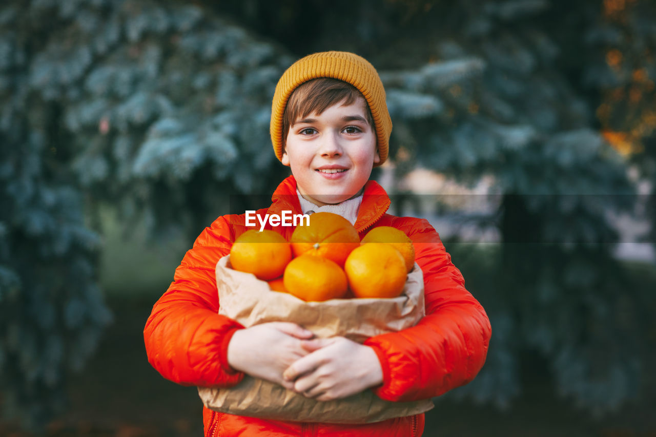 A boy in a bright orange jacket and a yellow hat holds a large package with oranges in his hands