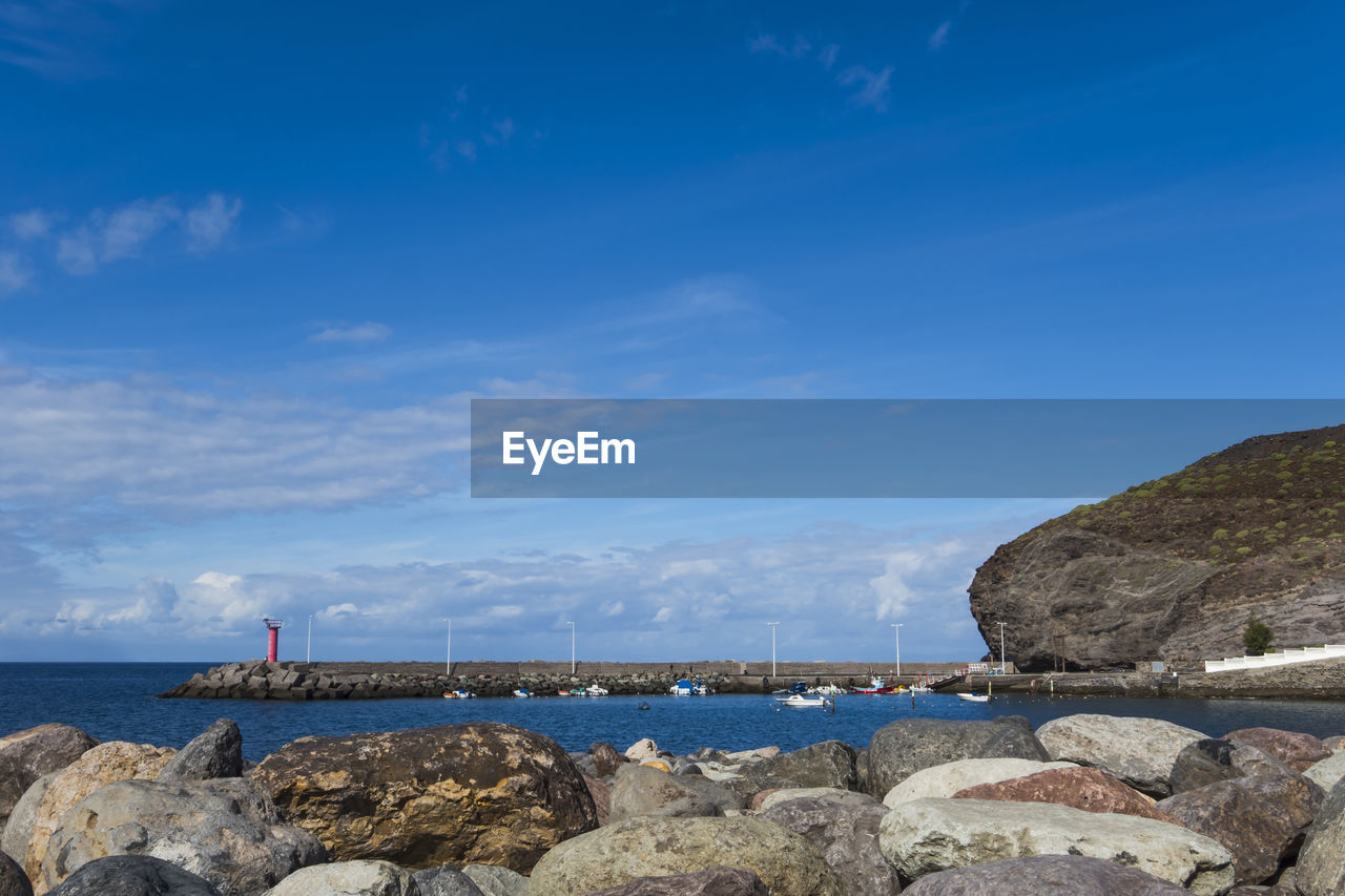 water, sky, sea, rock, beauty in nature, rock - object, solid, scenics - nature, blue, nature, tranquil scene, tranquility, cloud - sky, day, land, idyllic, outdoors, beach, non-urban scene, groyne