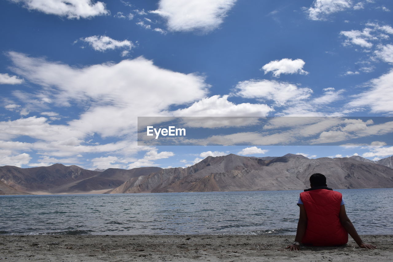 REAR VIEW OF WOMAN STANDING ON SEA AGAINST MOUNTAINS