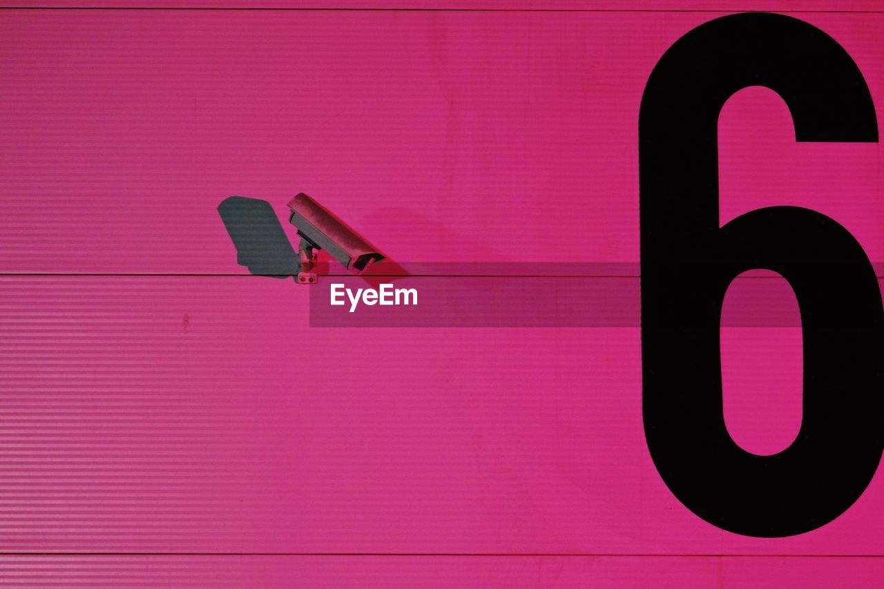 Close-Up Of Security Camera On Pink Wall