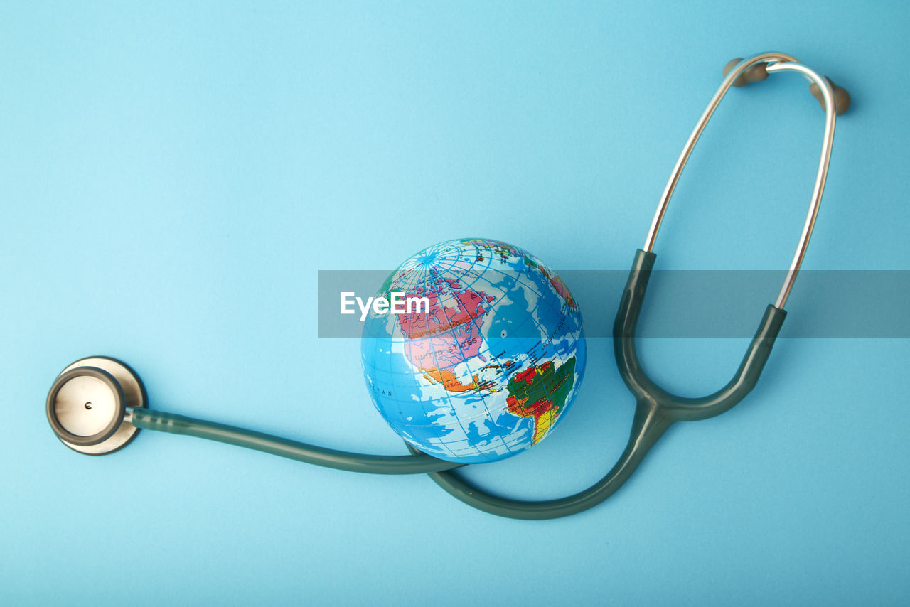 Close-up of globe with stethoscope over blue background