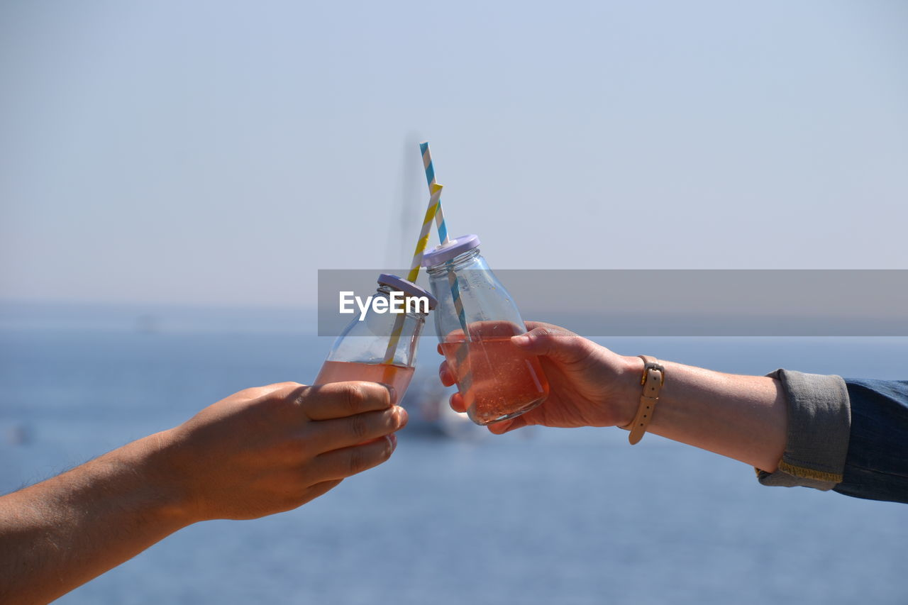 Cropped Image Of Friends Hands Toasting Drinks By Sea Against Sky