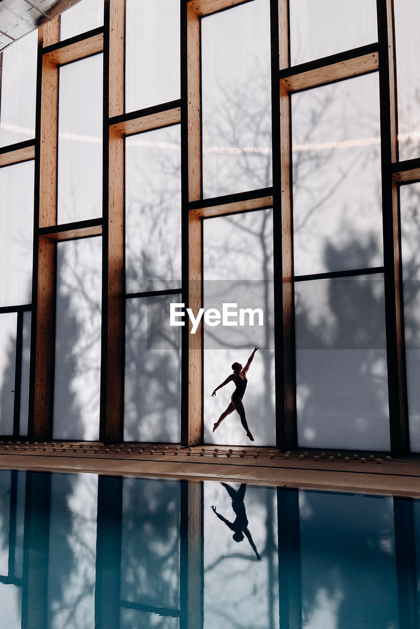 Woman in swimming pool against sky seen through window