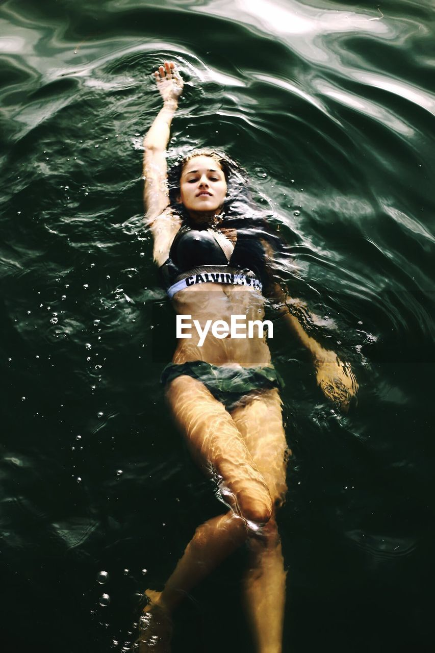 High Angle Of Young Woman Swimming In Sea