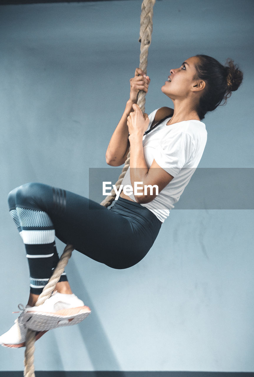 sport, one person, strength, lifestyles, healthy lifestyle, sports clothing, real people, indoors, exercising, full length, gym, determination, young adult, vitality, holding, young women, wellbeing, athlete, side view, skill, hairstyle, effort, body conscious