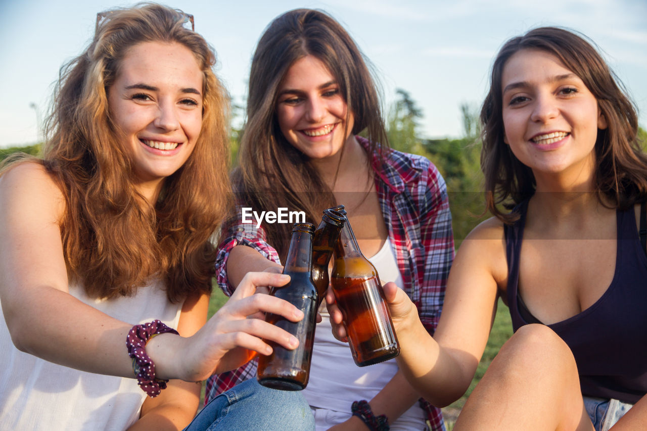 Portrait of happy young woman toasting beer bottle with female friends on field