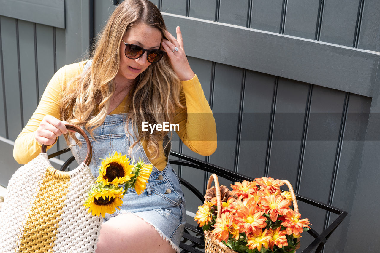 Young woman sitting by flowers against wall