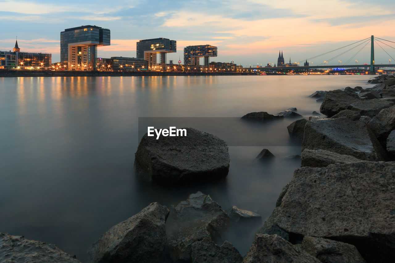 built structure, architecture, building exterior, water, sky, rock, solid, rock - object, sunset, cloud - sky, nature, city, river, building, dusk, no people, waterfront, outdoors, office building exterior, skyscraper