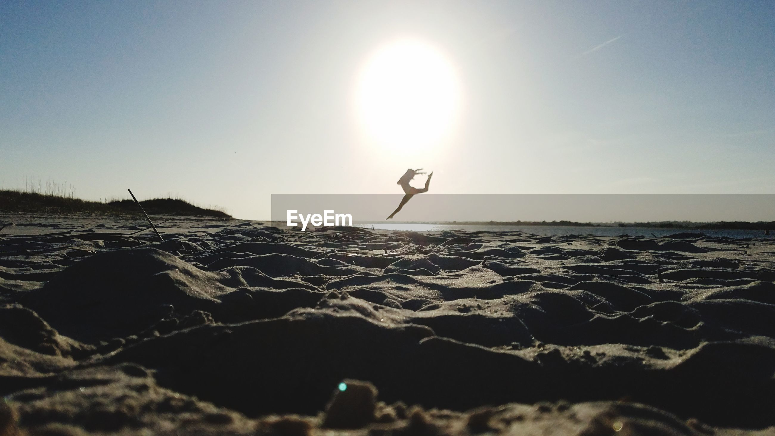 Woman jumping at beach against clear sky at sunset
