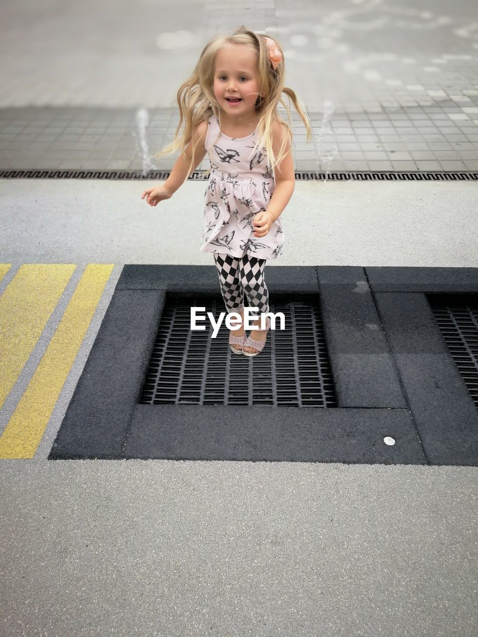 Full length of playful girl jumping over metal grate at street