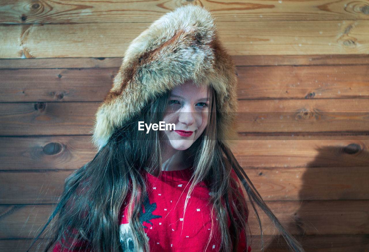 portrait, one person, smiling, looking at camera, happiness, hat, warm clothing, hair, clothing, headshot, winter, front view, wood - material, women, leisure activity, fur, long hair, young adult, emotion, fur hat, beautiful woman, hairstyle, teenager, hood - clothing