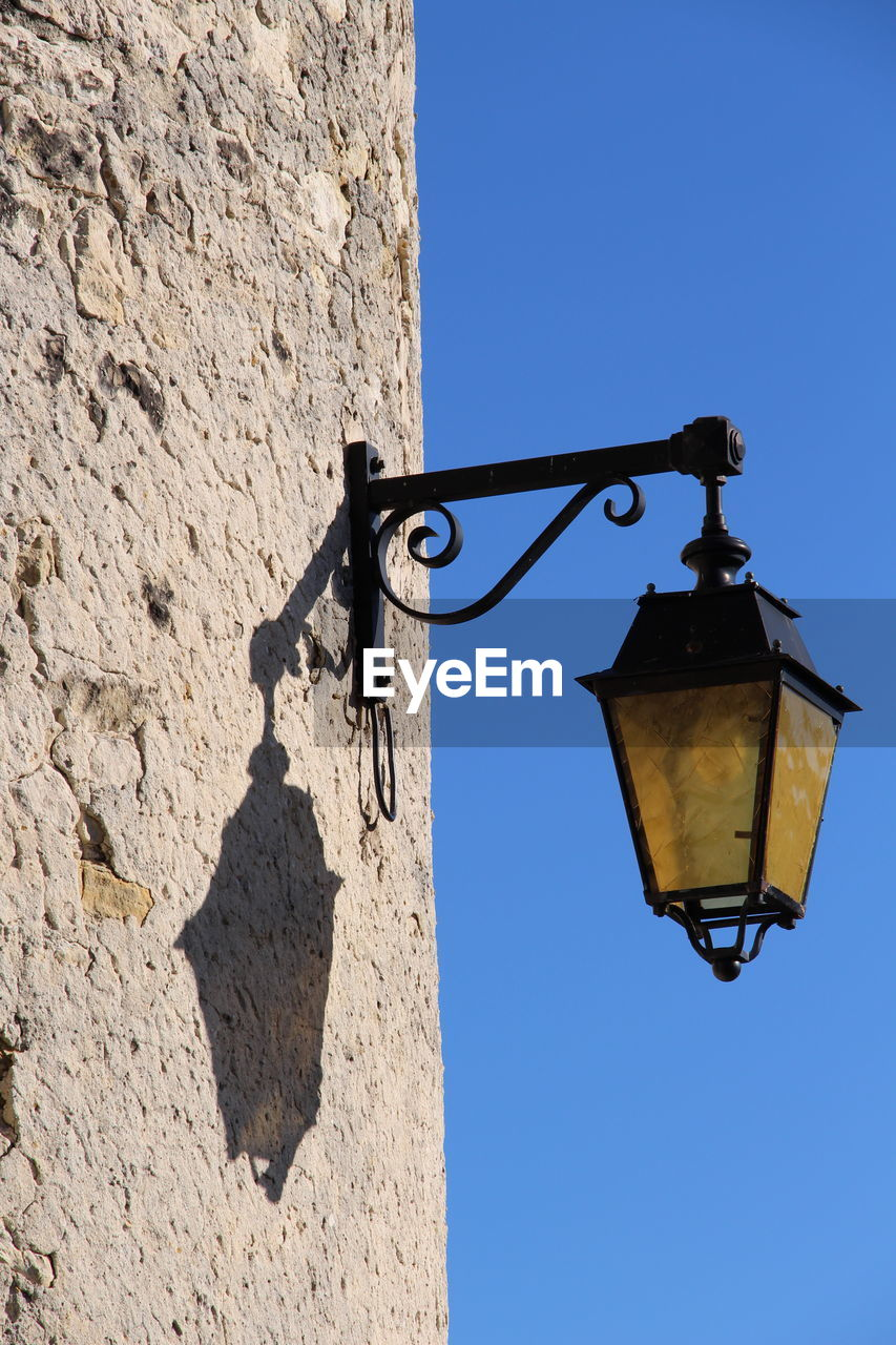 lighting equipment, sky, low angle view, built structure, nature, sunlight, architecture, wall - building feature, no people, day, clear sky, building exterior, old, electric lamp, shadow, blue, wall, street light, street, metal, outdoors, stone wall