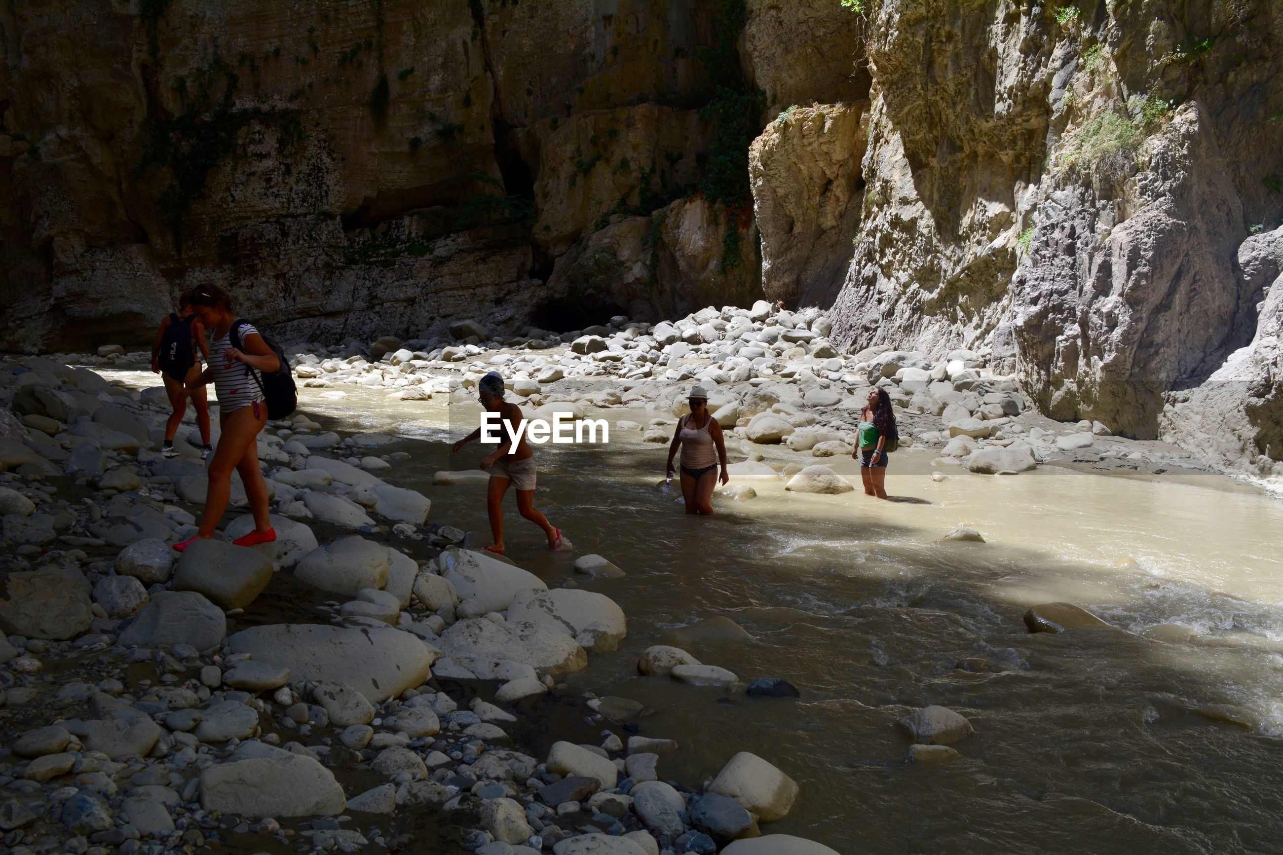Friends crossing river against rock formations