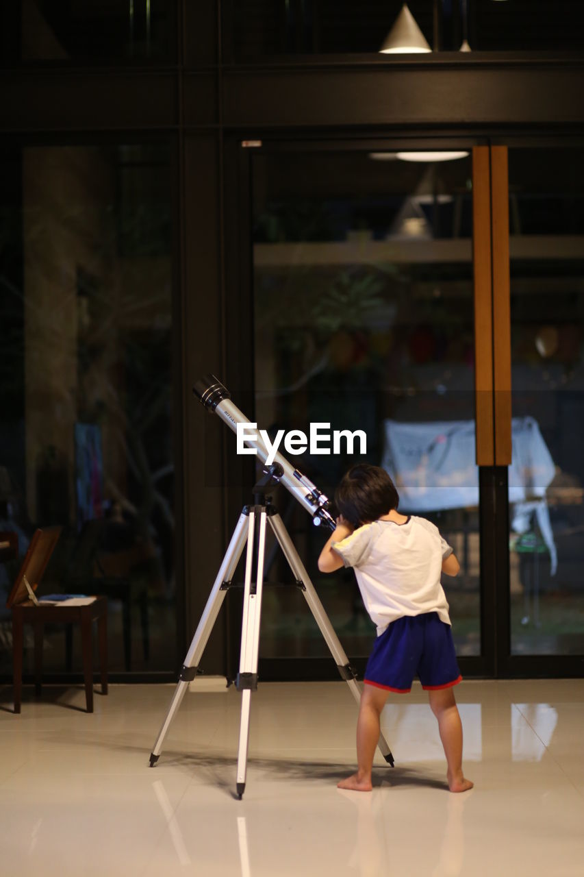 Rear View Full Length Of Boy Standing By Telescope On Floor