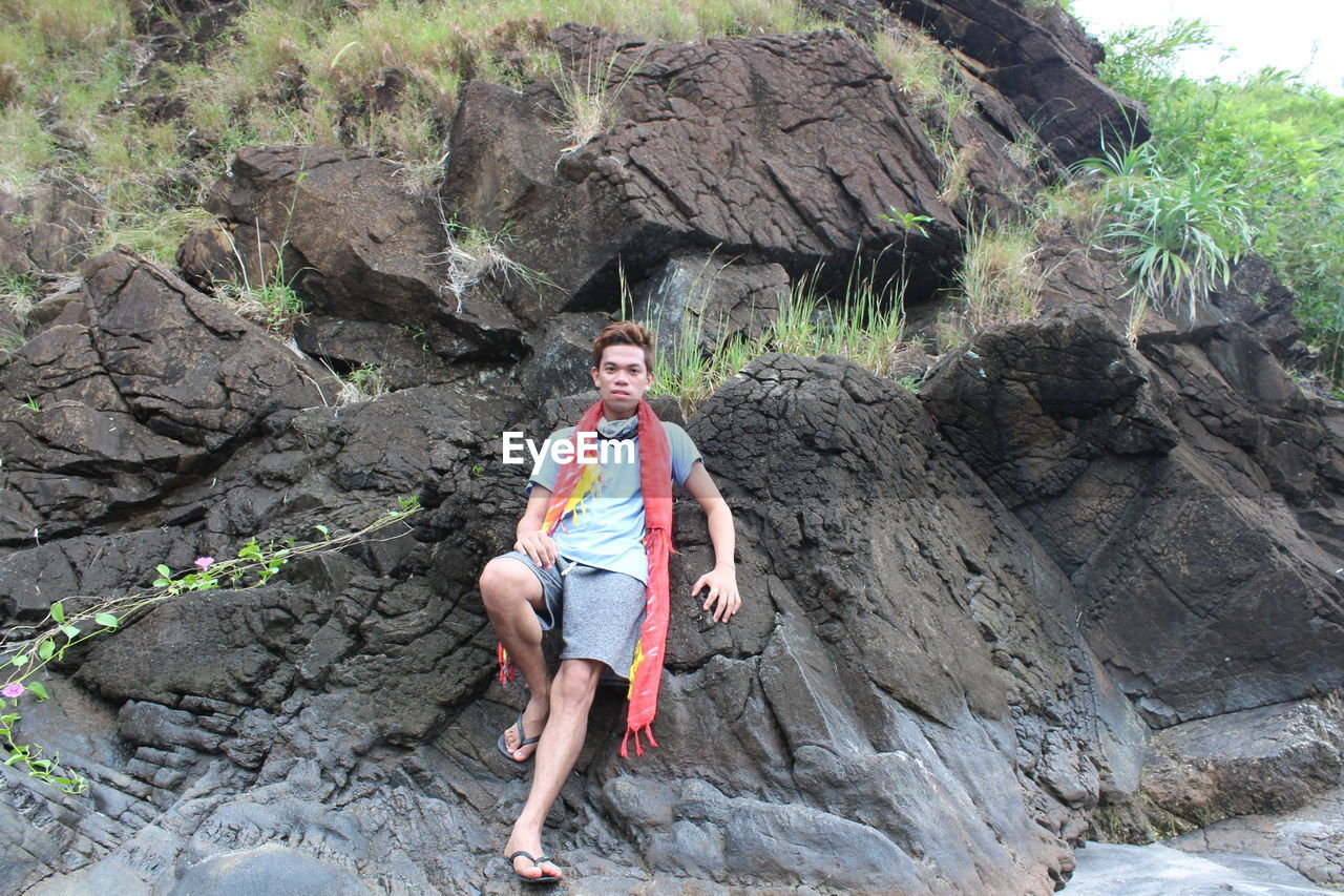 Portrait of young man leaning on rock