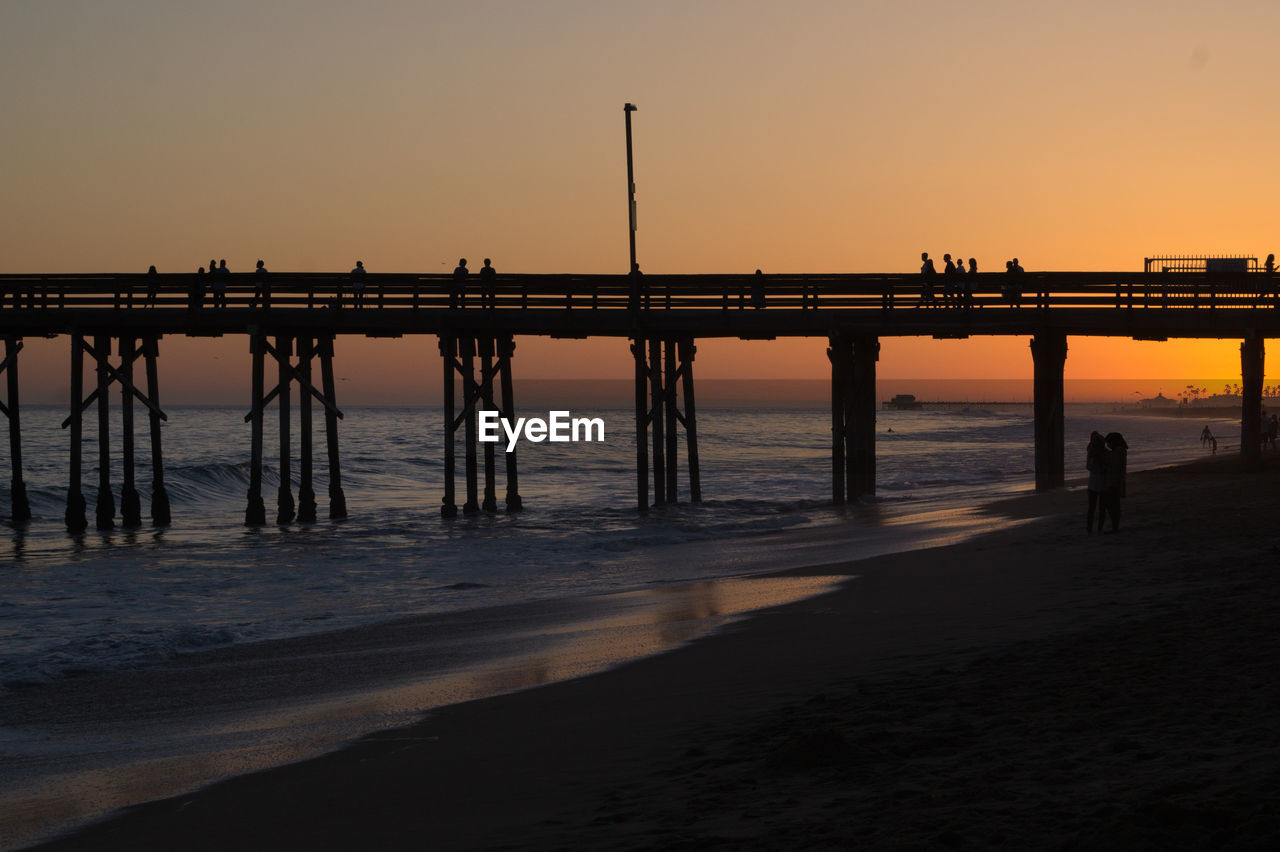 Silhouette Pier On Beach Against Clear Sky At Sunset