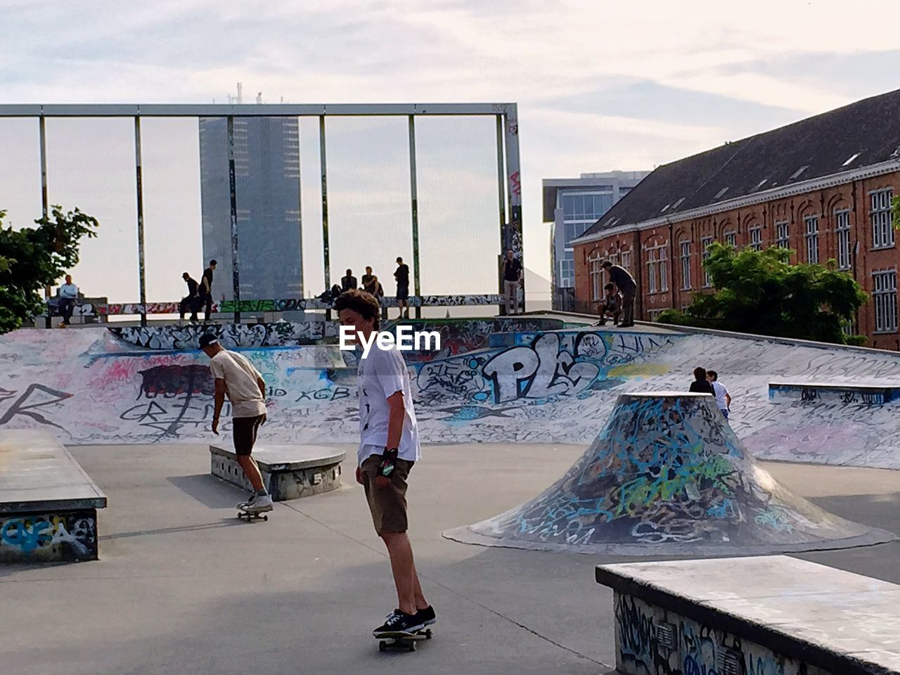 real people, built structure, architecture, art and craft, sky, day, casual clothing, building exterior, leisure activity, lifestyles, skateboard, skateboard park, full length, artist, outdoors, men, standing, women, one person, water, city, tree, young adult, people