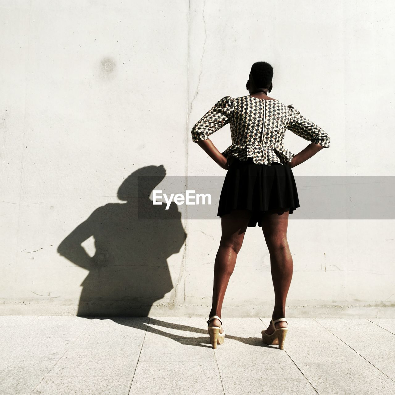 Rear View Of Woman With Hands On Hip Standing Against Wall On Sunny Day