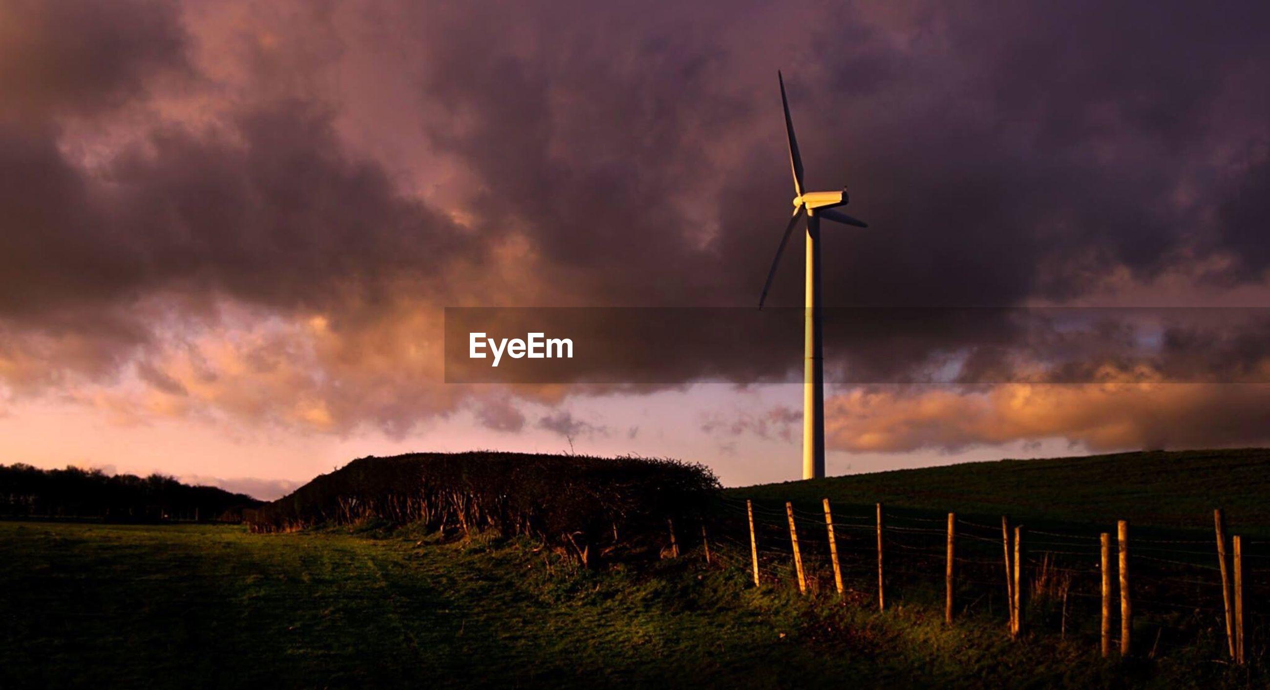 Wind turbine on landscape against purple sky