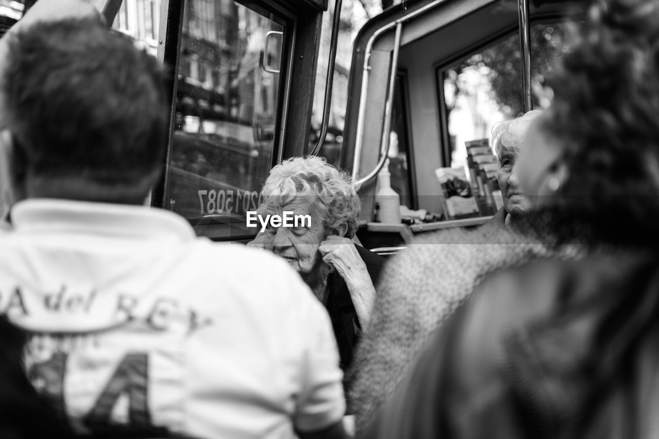 real people, rear view, selective focus, two people, transportation, men, public transportation, togetherness, day, sitting, domestic animals, pets, lifestyles, women, mammal, indoors, friendship, close-up, people