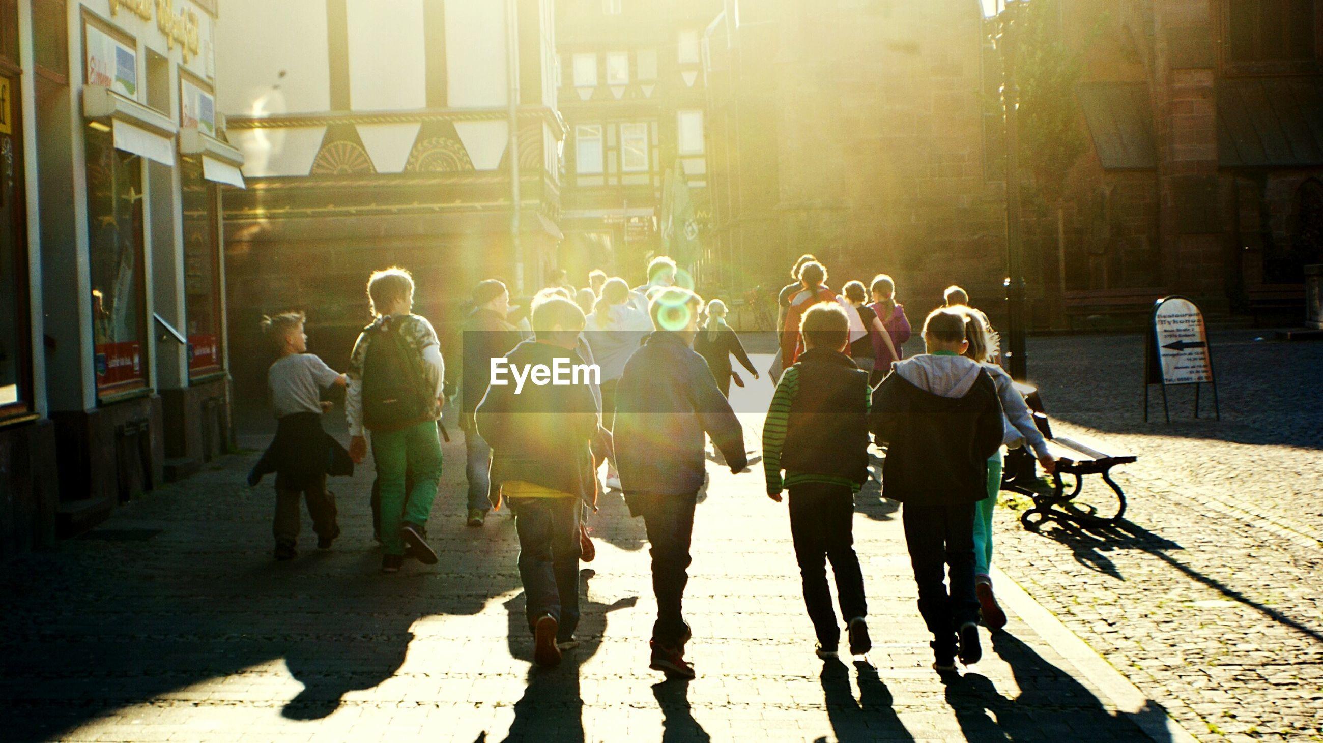 Rear view of children walking on city street by buildings