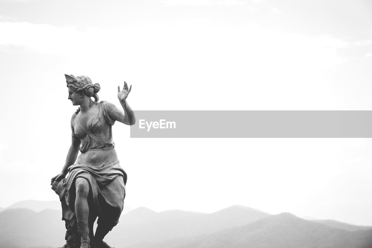 statue, sculpture, low angle view, outdoors, day, sky, mountain, clear sky, nature, no people