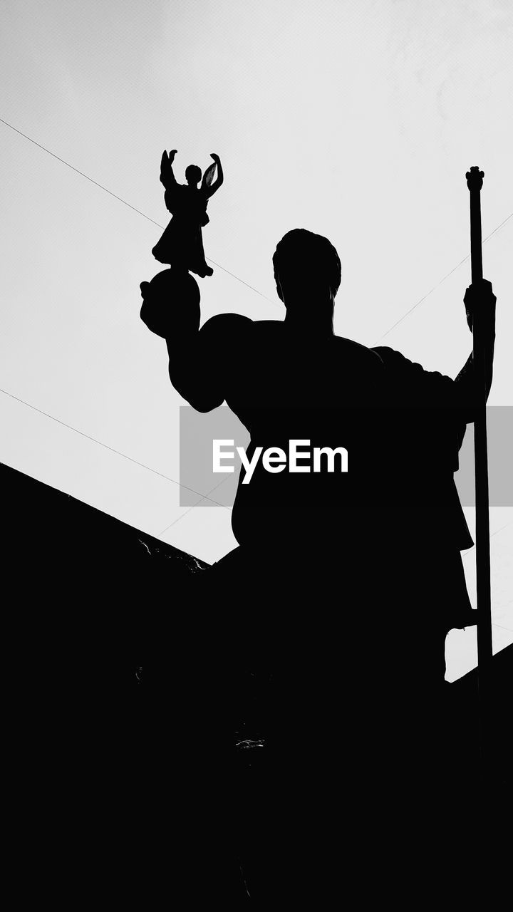 silhouette, low angle view, statue, clear sky, sky, outdoors, animal themes, one person, day, people