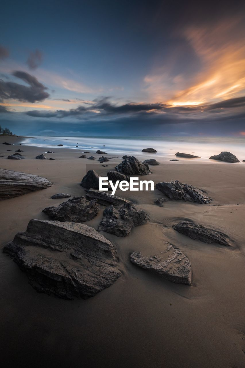 sky, scenics - nature, sunset, beauty in nature, tranquil scene, water, sea, tranquility, land, cloud - sky, beach, rock, solid, idyllic, non-urban scene, rock - object, nature, no people, long exposure, horizon over water