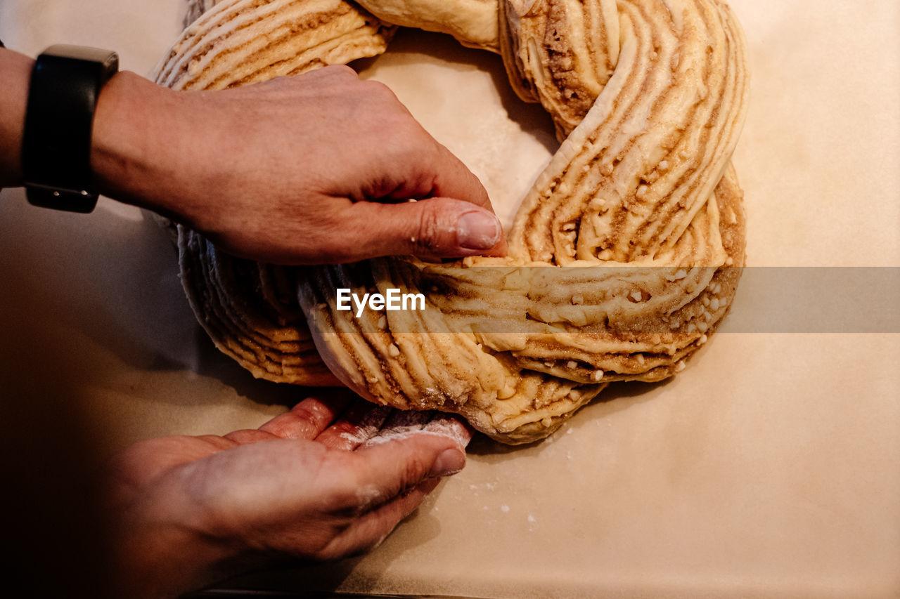 Close up of human hand weaving easter cake dough