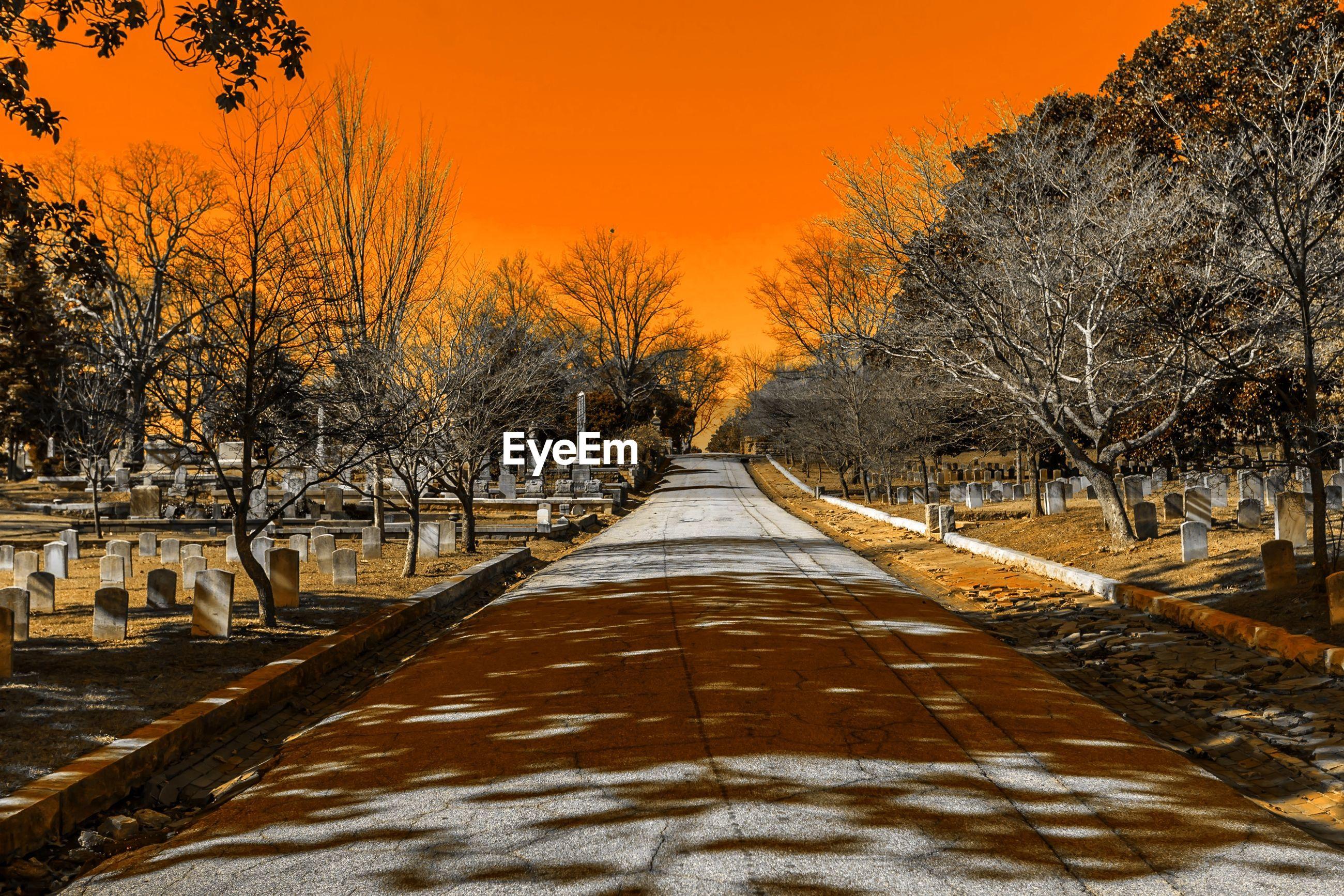 Empty footpath amidst cemetery against orange sky