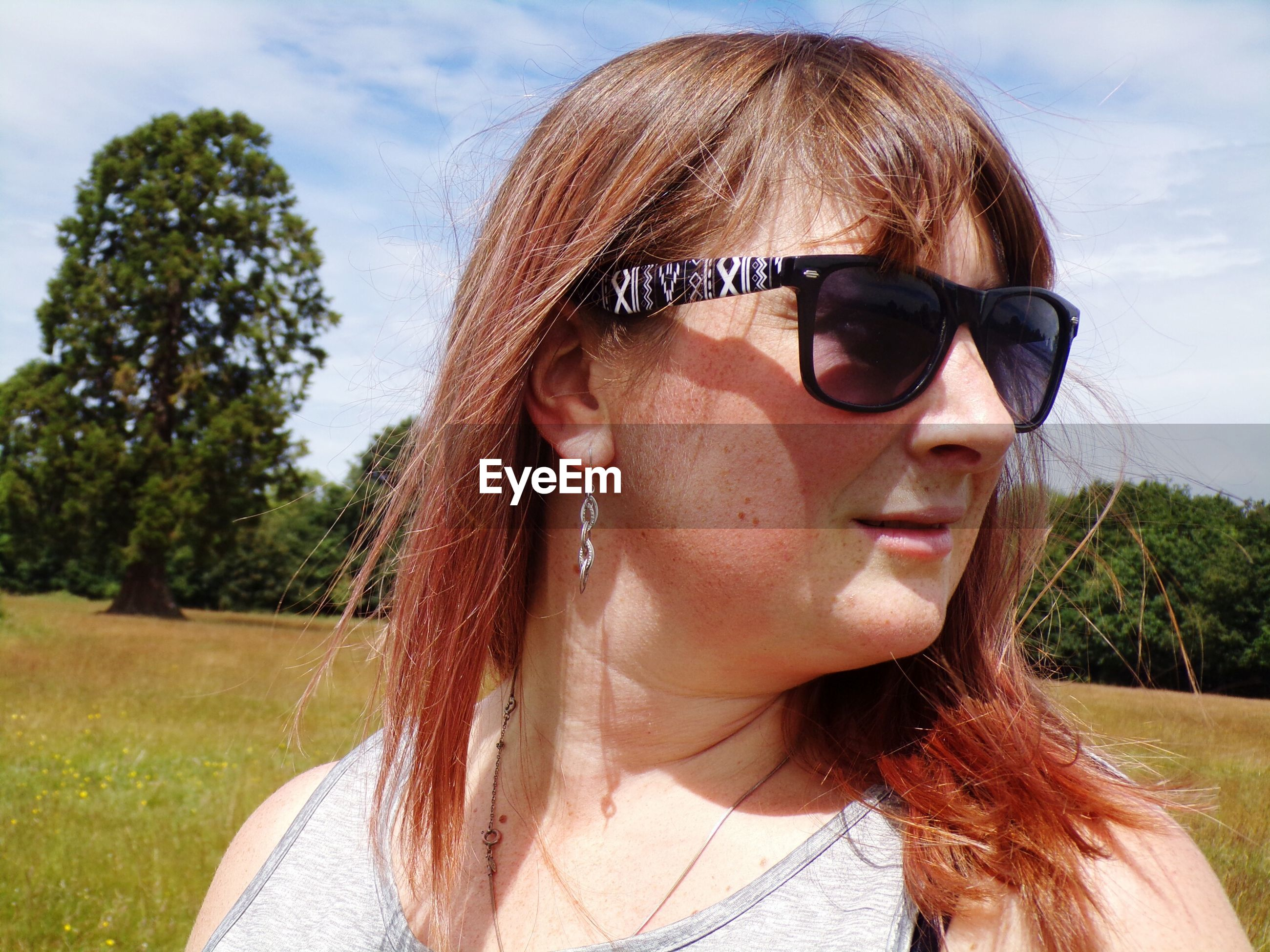 Close-up of woman wearing sunglasses looking away on field