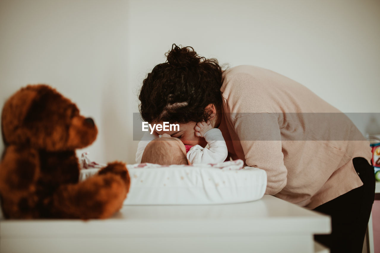 indoors, childhood, child, real people, mammal, domestic animals, furniture, one person, lifestyles, domestic, pets, relaxation, men, sitting, headshot, canine, women, dog, home interior, teddy bear, innocence