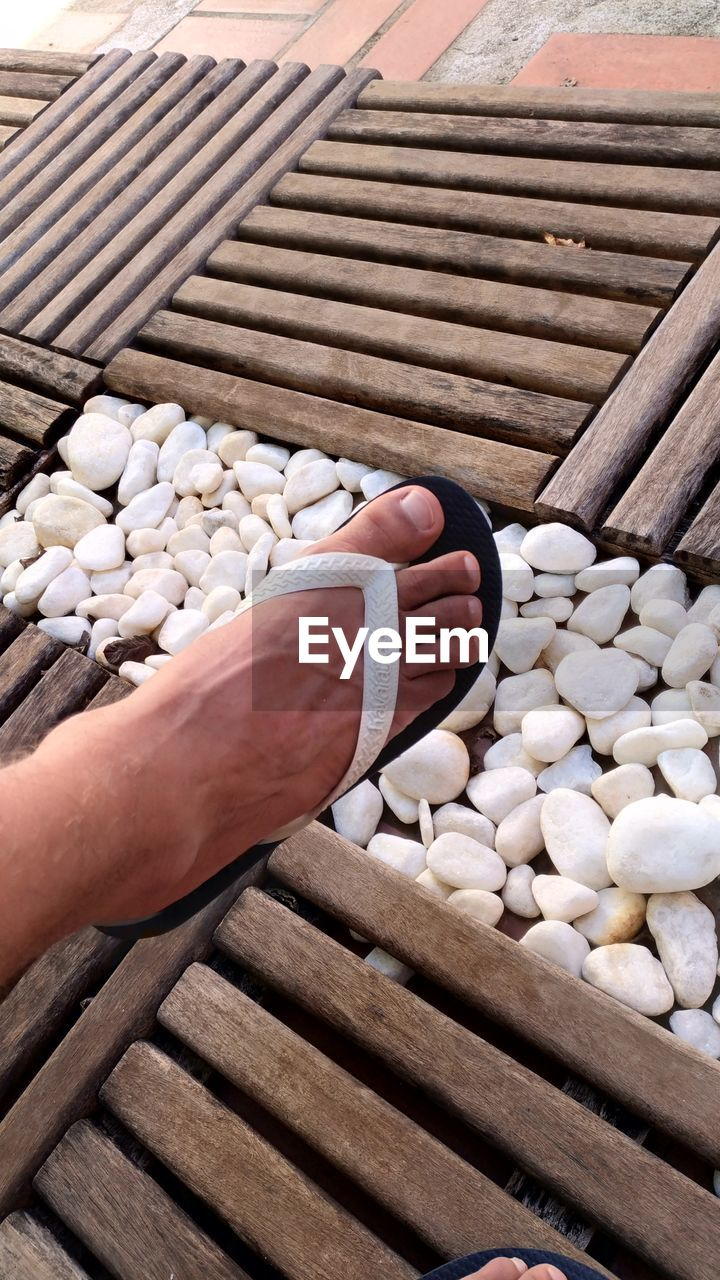 Low Section Of Man Over Pebbles