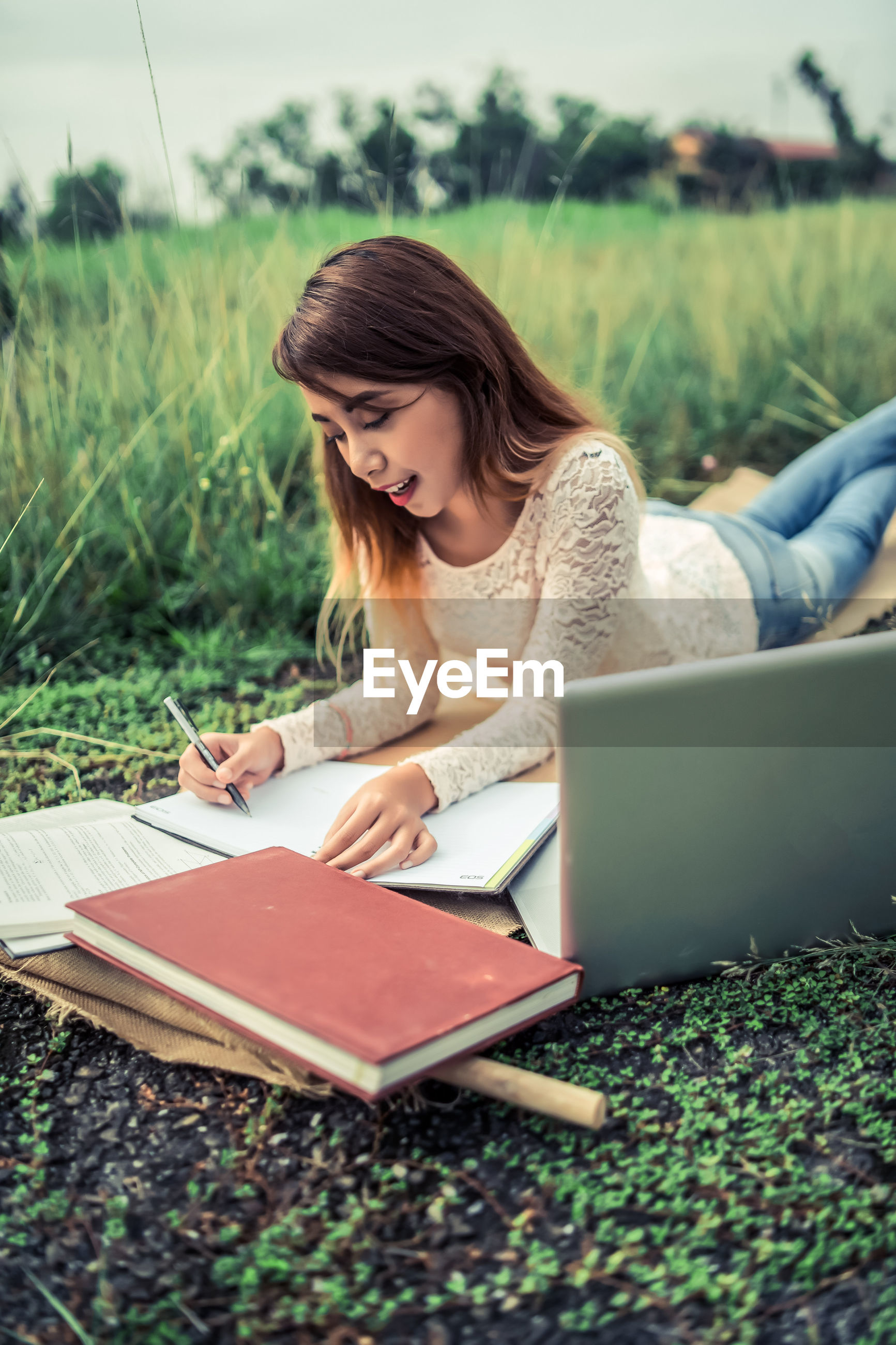 Young woman writing in book by laptop on field