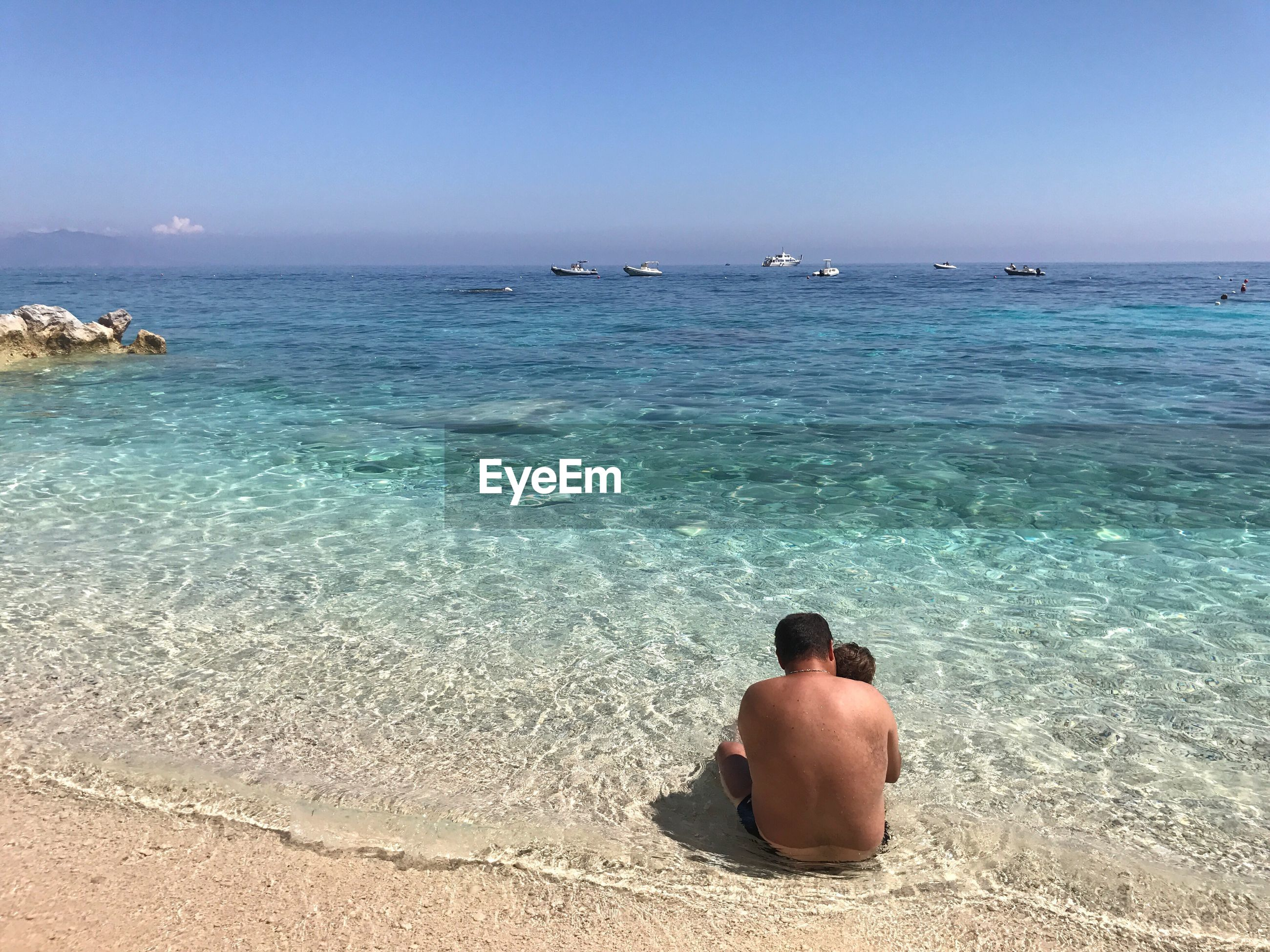 Rear view of shirtless father sitting with son on sea shore at cala mariolu