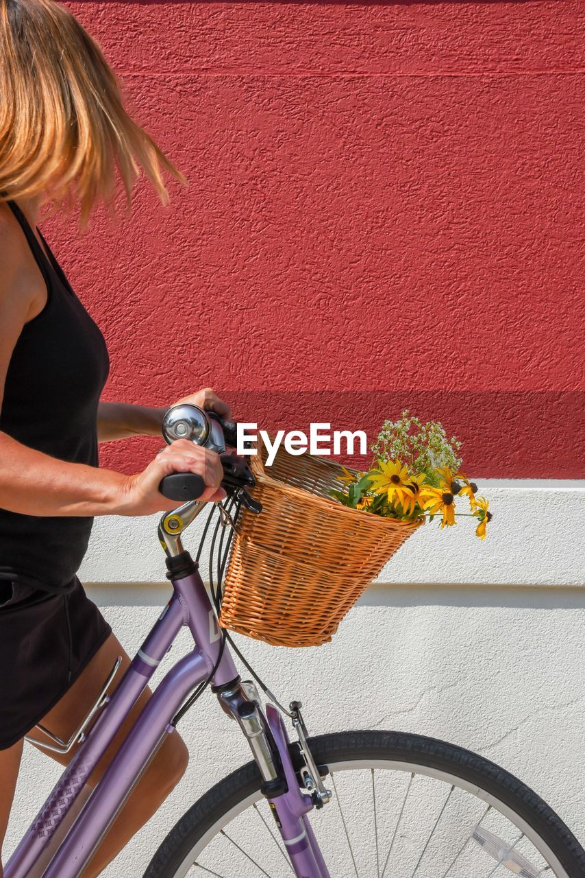 MIDSECTION OF WOMAN RIDING BICYCLE IN BASKET