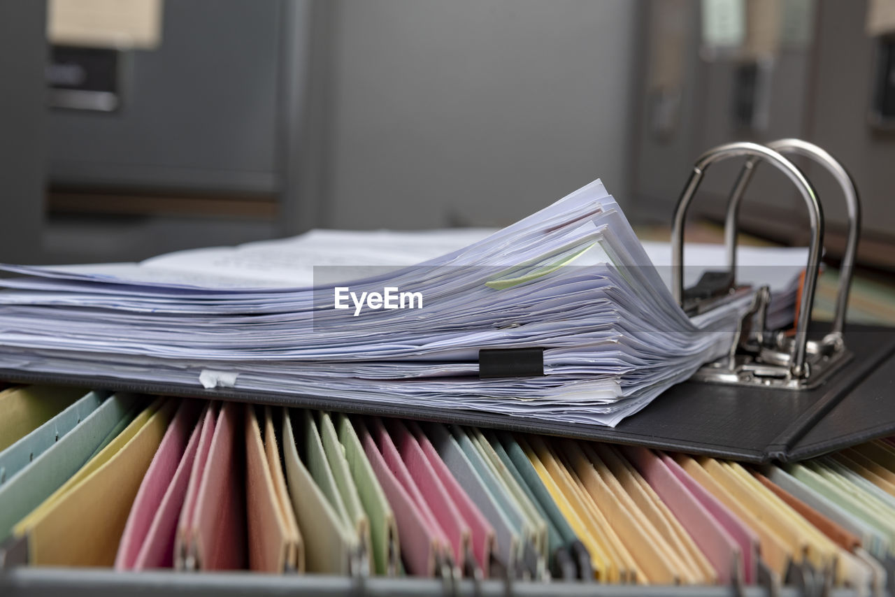 Close-up of open ring binder on filing cabinet in office
