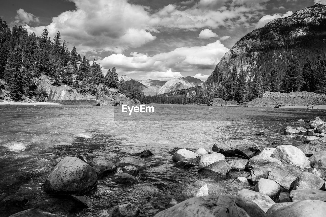 water, rock, beauty in nature, mountain, sky, cloud - sky, scenics - nature, tree, tranquility, rock - object, tranquil scene, solid, nature, day, no people, plant, non-urban scene, environment, mountain range, outdoors, flowing water