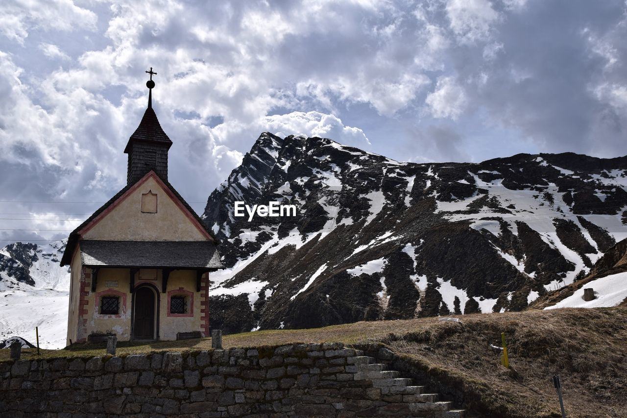 View of church by snowcapped mountain