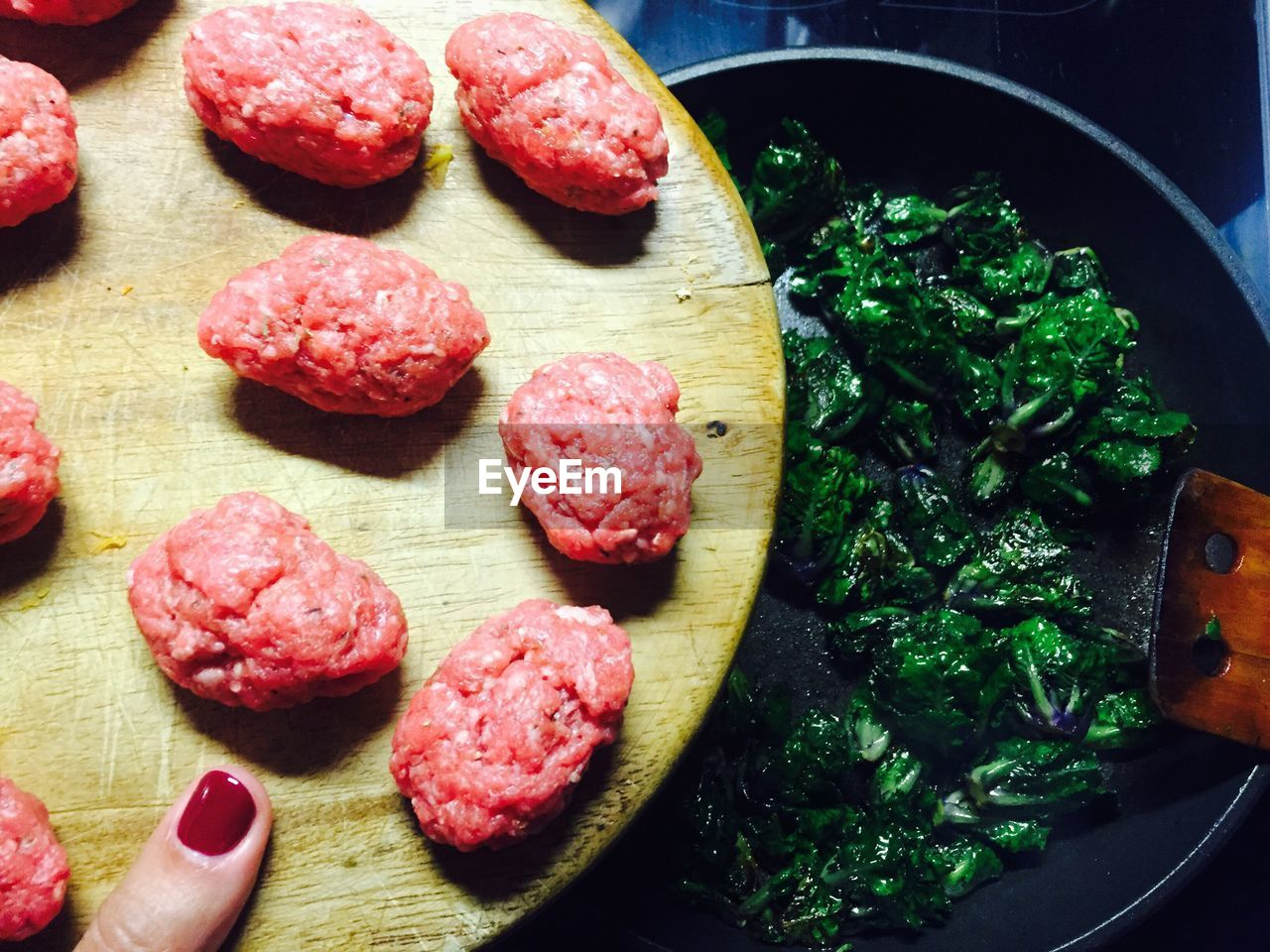 Cropped Image Of Woman Holding Meat On Cutting Board While Preparing Food