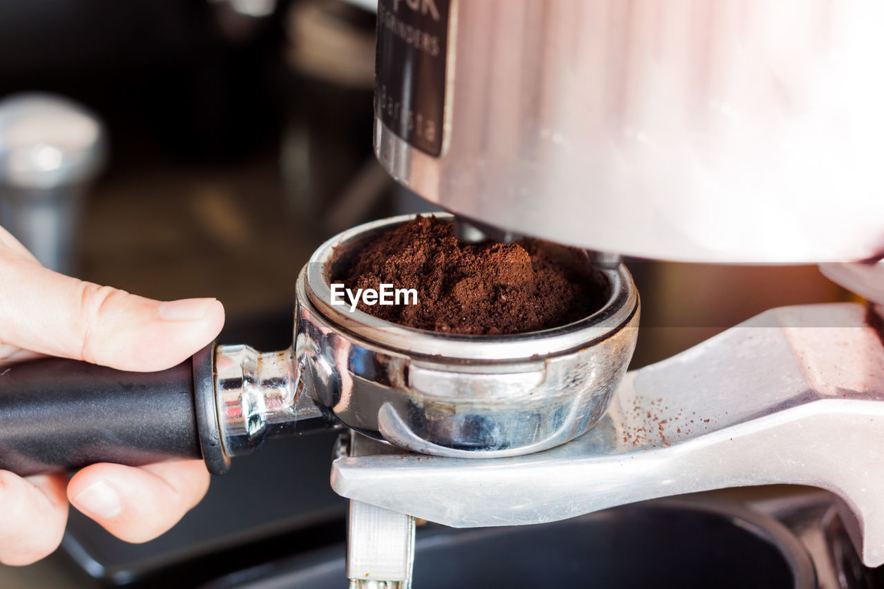 human hand, hand, human body part, food and drink, one person, preparation, holding, coffee maker, appliance, real people, unrecognizable person, machinery, indoors, food, body part, coffee, freshness, coffee - drink, making, finger, barista, caffeine