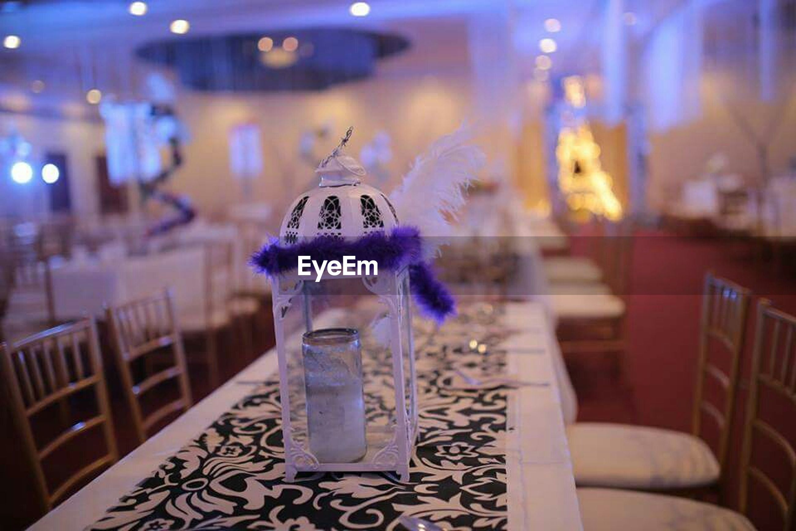 indoors, focus on foreground, illuminated, night, table, close-up, incidental people, selective focus, blue, glass - material, restaurant, lighting equipment, drinking glass, no people, decoration, still life, home interior, transparent, celebration, reflection