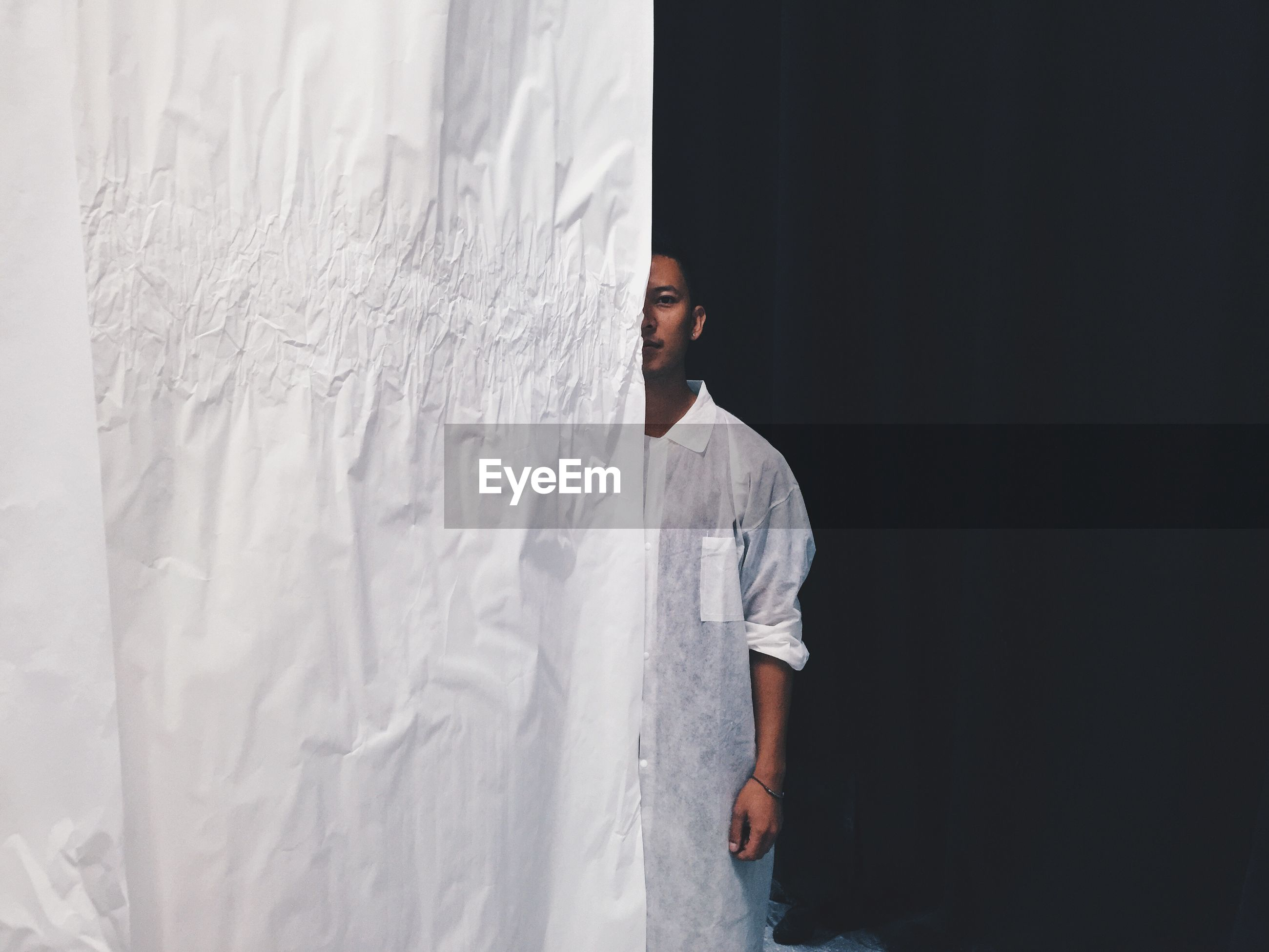 Portrait of young man standing behind curtain