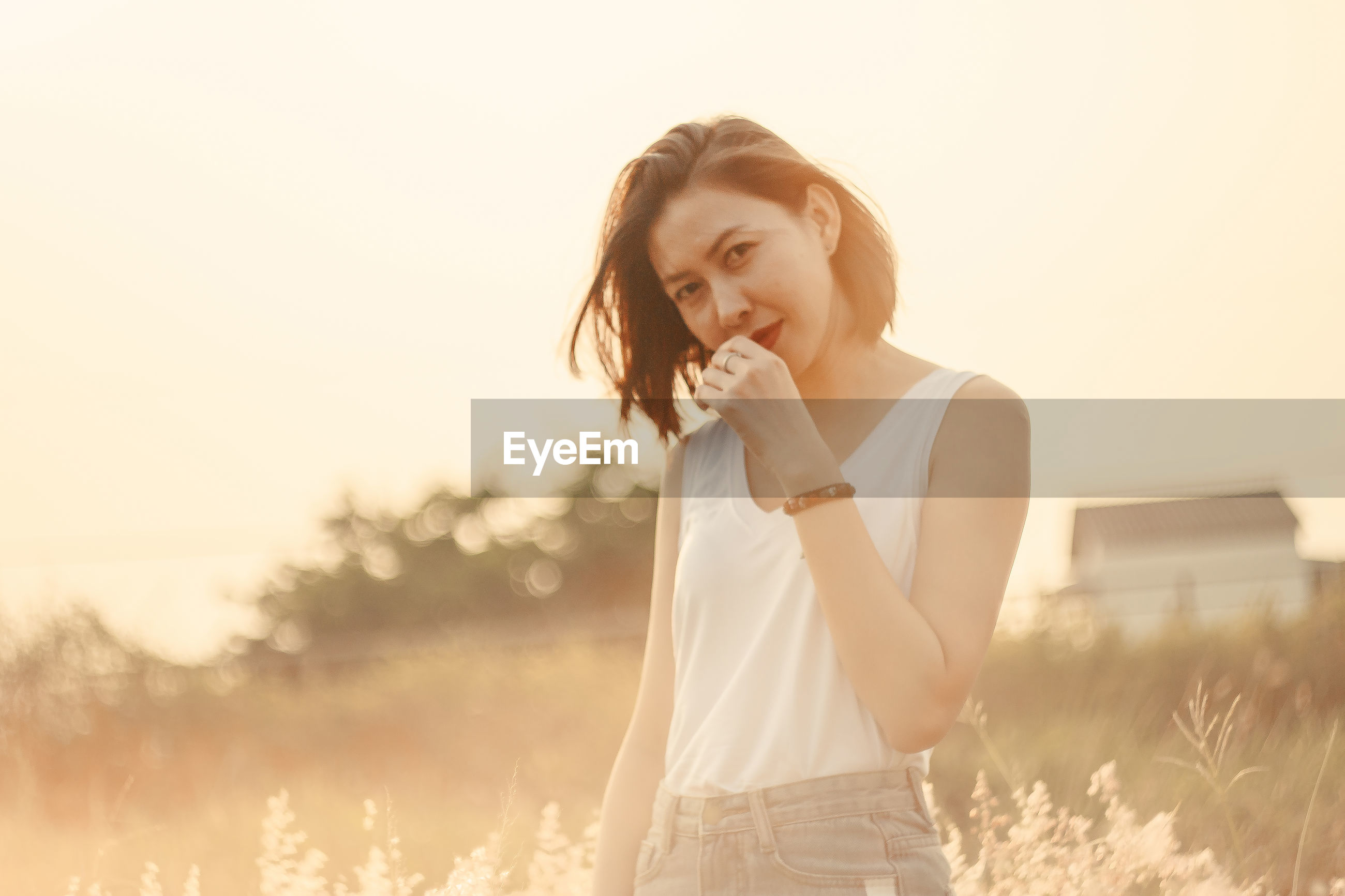 Portrait of woman standing against clear sky during sunset