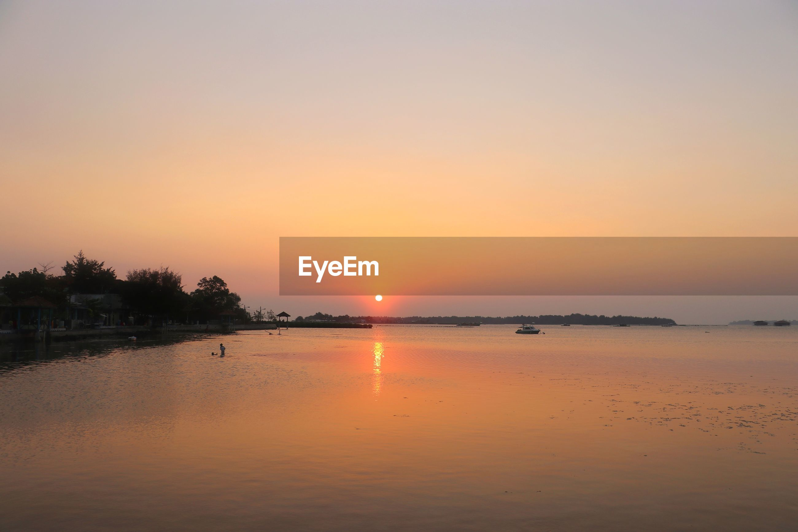 SCENIC VIEW OF LAKE AGAINST ORANGE SKY DURING SUNSET
