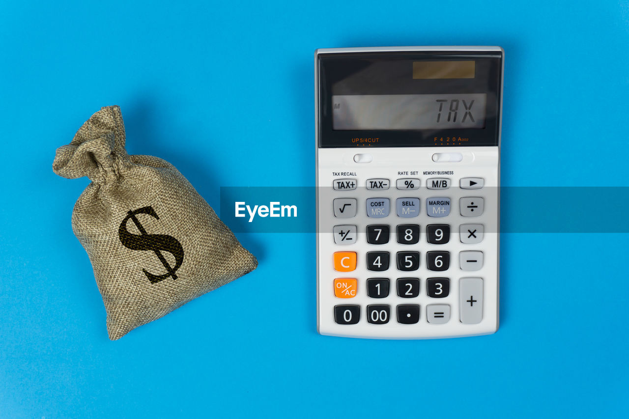 Directly above shot of calculator by sack with dollar sign against blue background