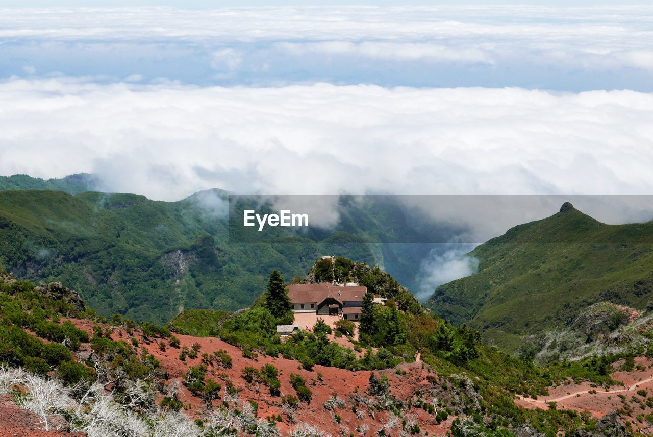 High Angle View Of House On Hill Against Cloudscape